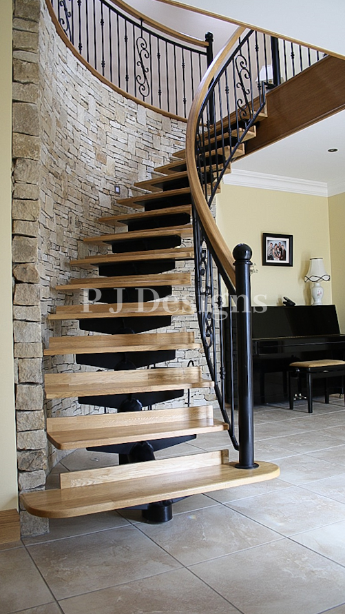1/4 Turned single spine Staircase curved around a stone feature wall. This staircase has metal balustrades with oak steps and handrail to finish.