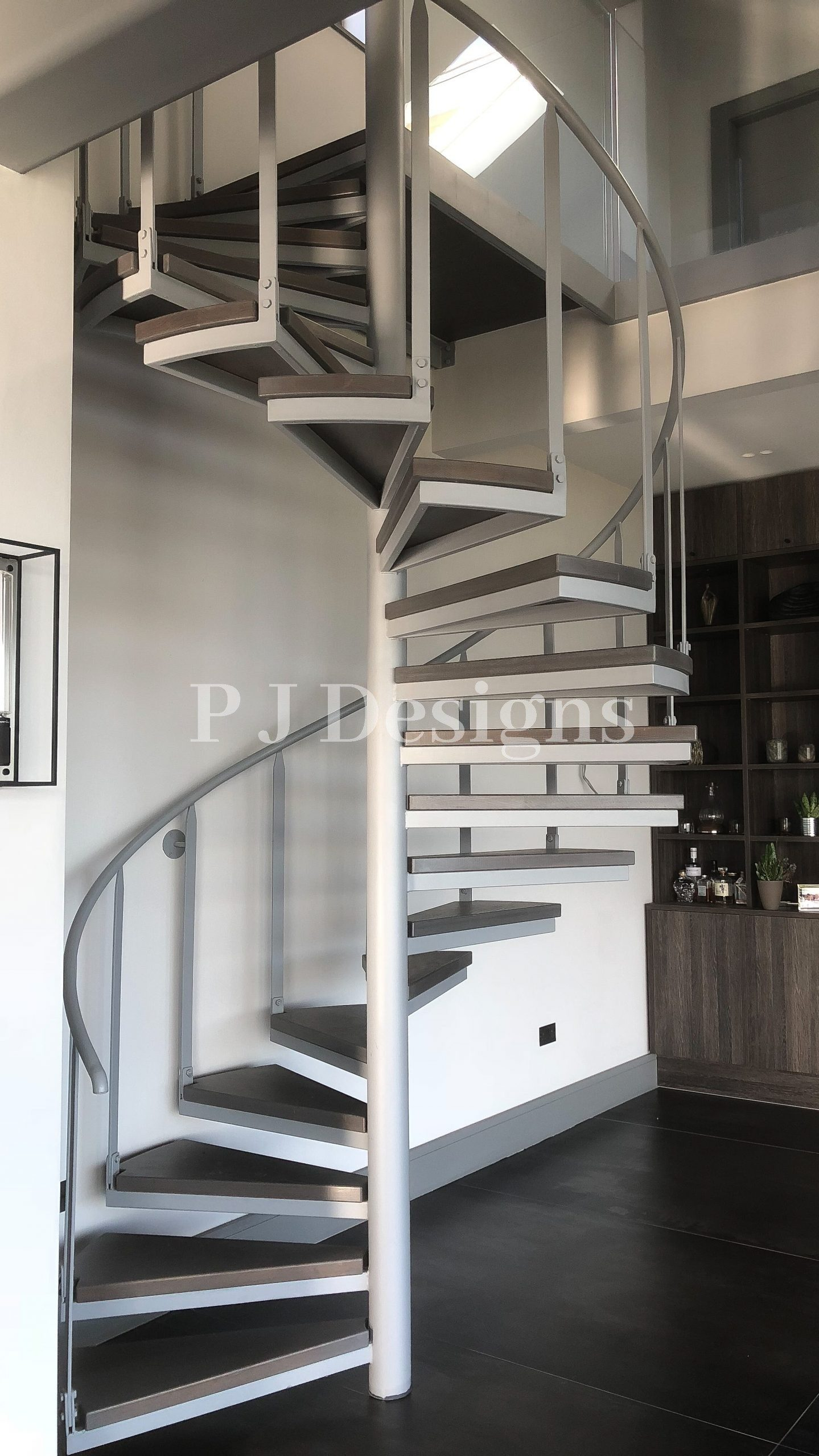Metal Spiral Staircase finished in a Grey/White colour with simplistic handrails and balustrades coming up from the end of each step, to add to the tidy and modern ascetic to the room.