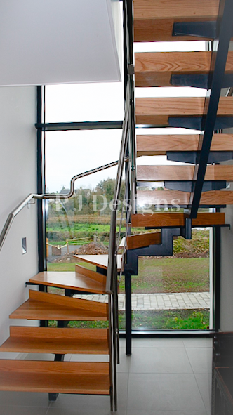 Metal Single Spine Staircase with oak steps, six that are wondering around the window with a stainless steel handrail to finish.
