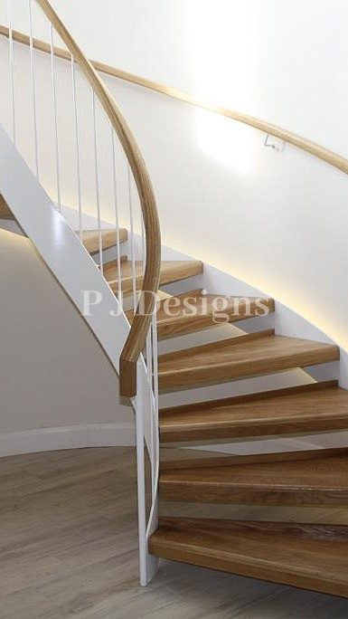 White double string Curved Staircase which is curved around an alcove with a light behind to give a glowing effect without being too over powering. Finished with oak steps.