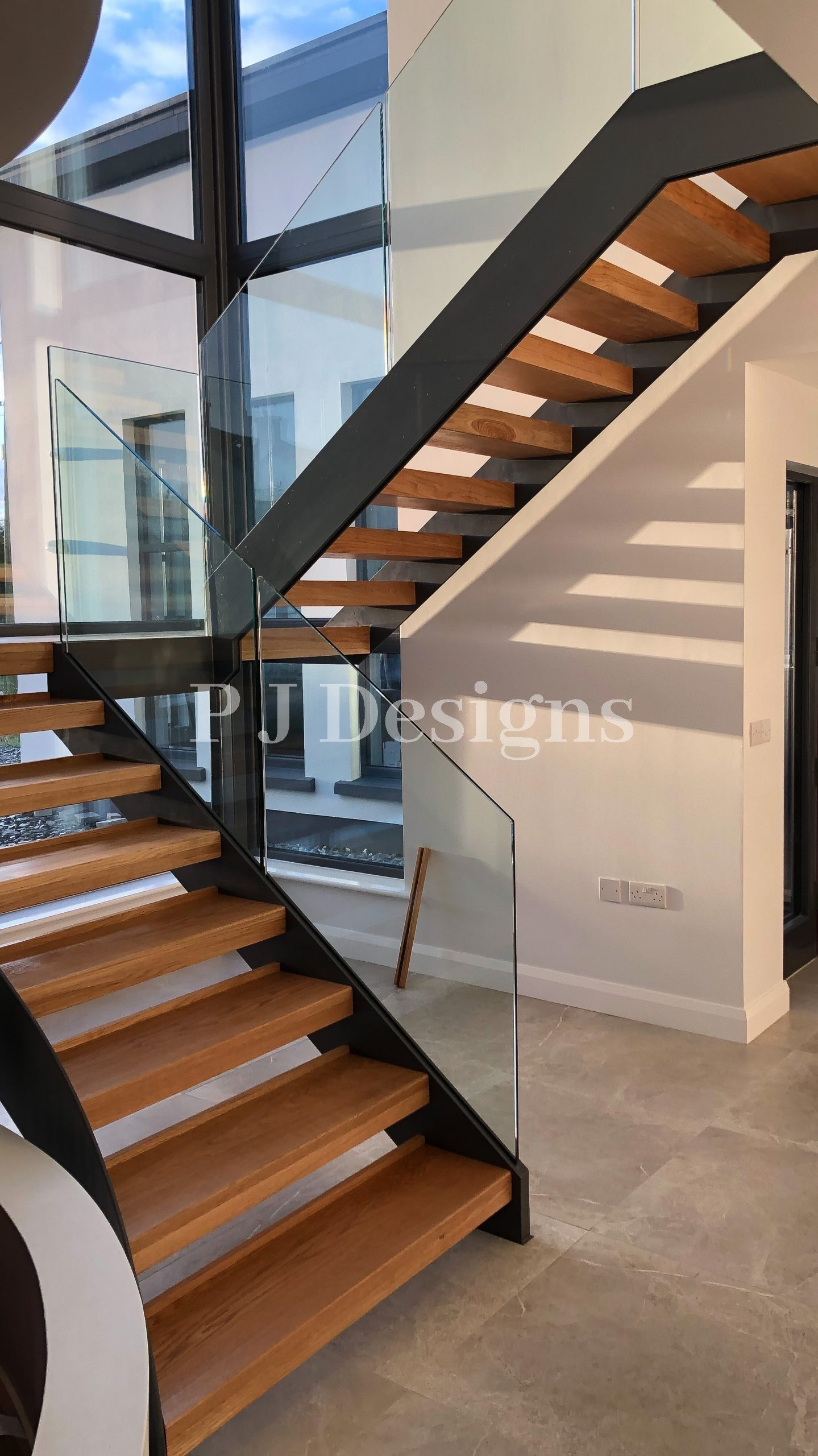 Double String Metal Staircase finished in a dark grey colour with oak steps and glass balustrade.