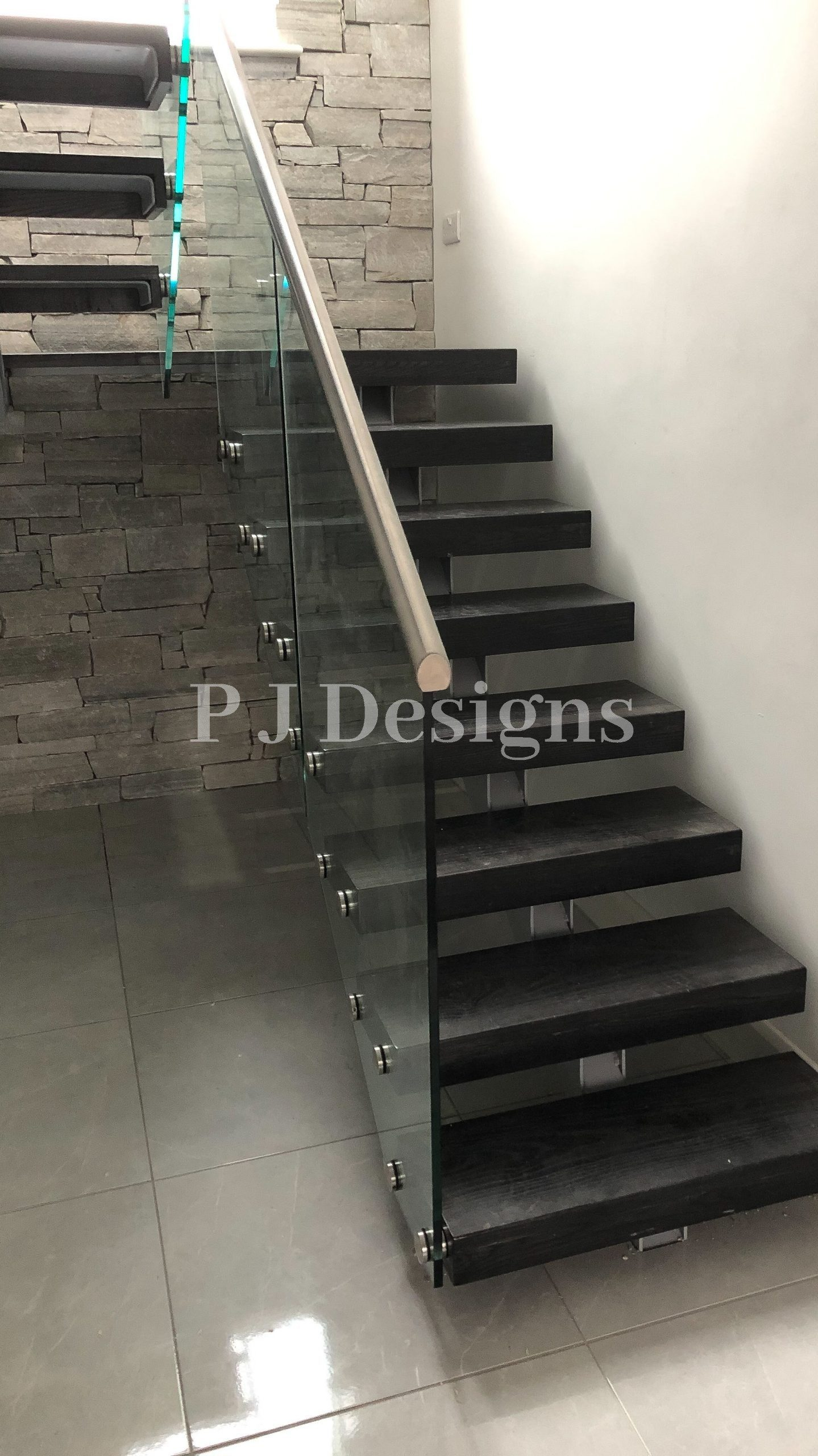 Single spine with a detail Rione Plate Design under the black ash steps and a landing with a Glass and Stainless Steel balustrade